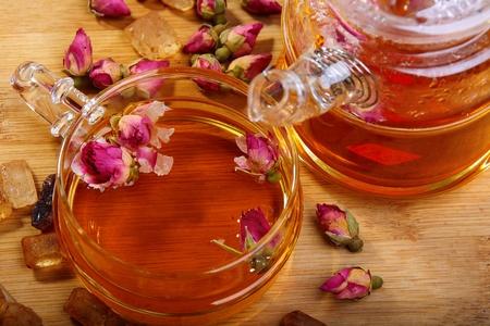 Tee mit Knospen von Rosen und brauner Zucker. Lizenzfreie Bilder - 9071671