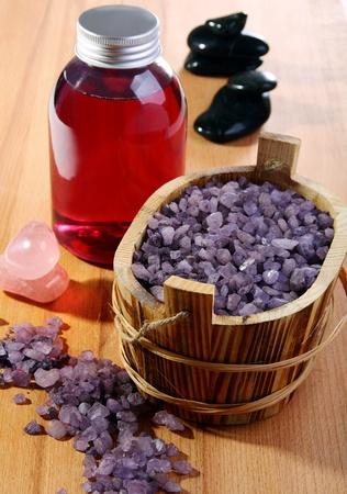 Violet bath salt in a basket on a wooden surface.