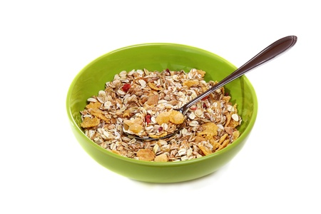 Muesli with fruit and berries in a green cup on a white background. Standard-Bild