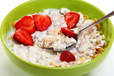 Muesli with fruit and berries in a green cup on a white background.  photo