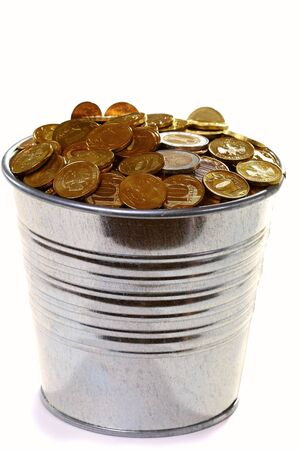 Zinc bucket of gold coins isolated on a white background. photo