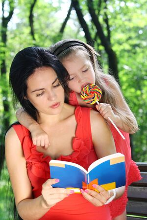 Little girl and mother reading the book in the garden.