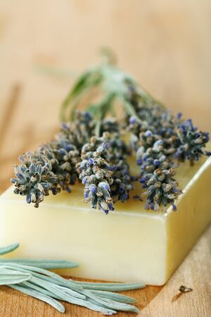 Sprigs of lavender and soap on a wooden table. photo