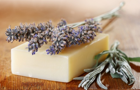 Sprigs of lavender and soap on a wooden table.