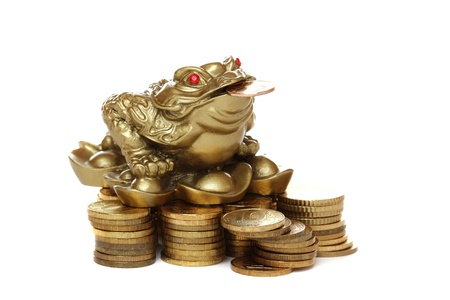 Feng Shui frog sitting on money �solated on white background.