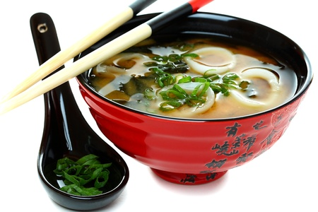 Miso soup with seafood and green onions on a white background. photo
