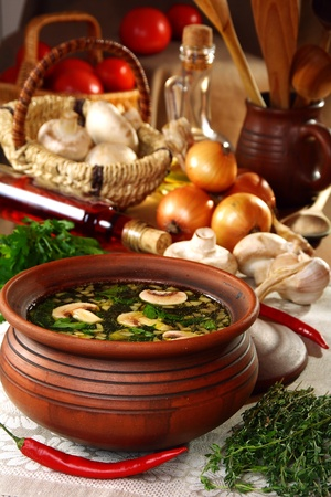 Mushroom soup in a ceramic pot on a wooden table.