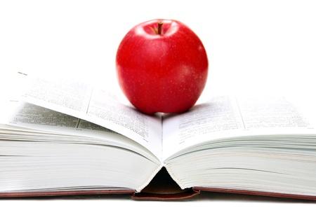 Czerwone jabłko na otwartą książkę na białym tle.