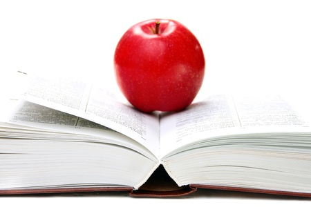 Red apple on an open book on white background.