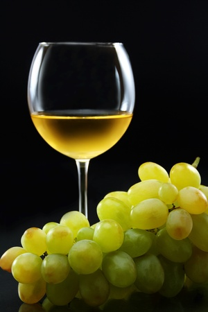 Glass of white wine and a bunch of grapes on a black background.