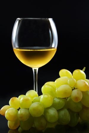 Szkło wina białego i kiść winogron na czarnym tle.