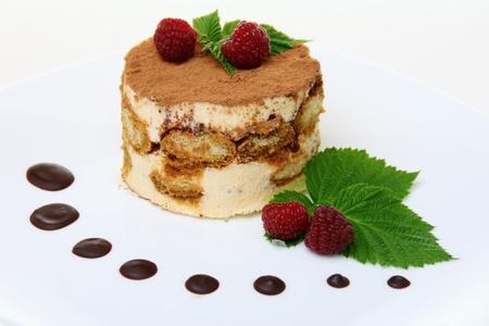 Tort Tiramisu z malin na białym talerzu.