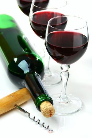 Butelka wina, kieliszki i korkociąg na białym tle.