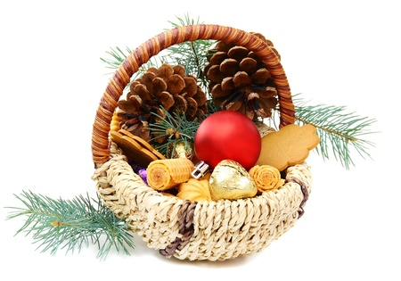 Christmas basket with candies, cookies and spruce branches on a white background.