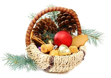 Koszyk Bożego Narodzenia z cukierki, ciasteczka i świerkowych gałęzi na białym tle.