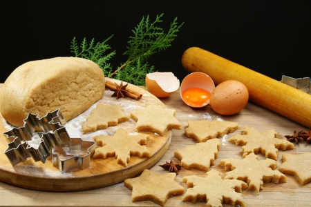 Christmas baking background with dough, cookie cutters and spices. photo