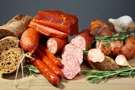 salchichas: Bodegón con salami, salchichas, baguette y Romero sobre una mesa de madera.