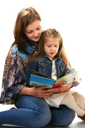 Young woman and little girl reading a book on a white background. Standard-Bild