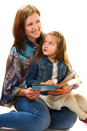 Young woman and little girl reading a book on a white background. photo