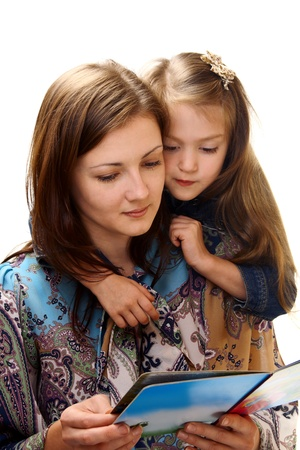 Young woman and little girl reading a book on a white background. Stock Photo