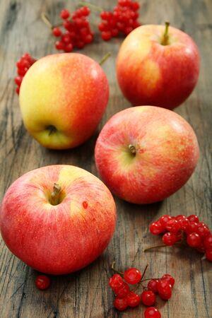 Czerwone jabłka i żurawiny na starej płycie drewnianej.