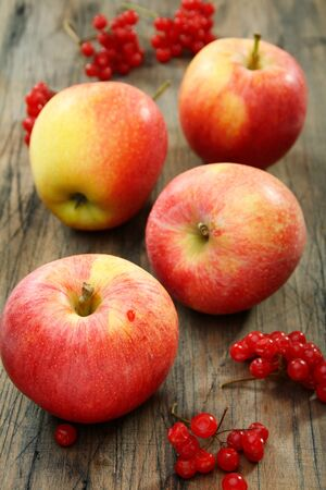 Red apples and cranberry on an old wooden board.  photo