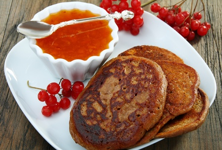Buckwheat pancakes with apricot jam on a wooden table. Stock Photo
