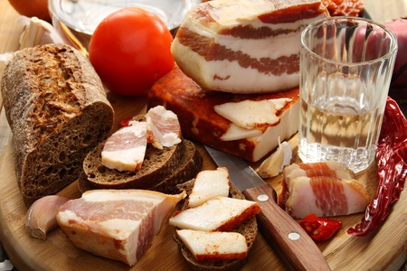 Glass of vodka bacon on rye bread on a wooden board. Stock Photo