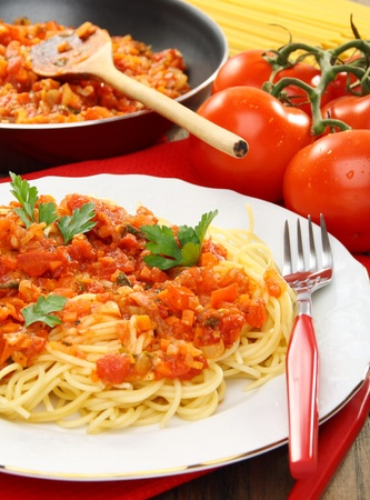 Spaghetti with sauce and ripe tomatoes on a wooden table.