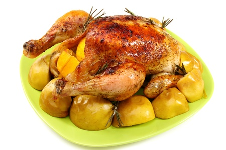 Chicken stuffed with lemons, apples and rosemary on white background. photo