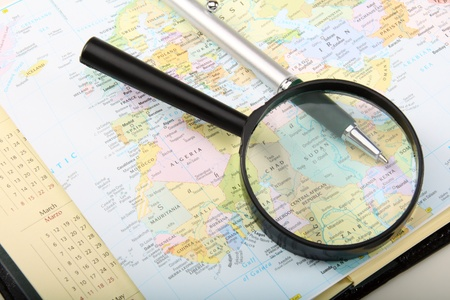 Diary, pen and magnifying glass on a map.