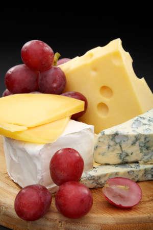 tabla de quesos: Los diferentes tipos de queso y uvas en una tabla de madera. Foto de archivo