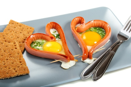 Two sausages in a heart-shaped fried eggs with green onions. Stock Photo