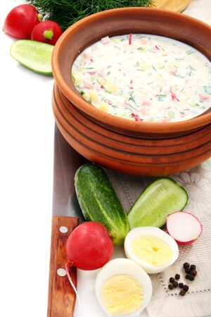 okroshka: Cold yogurt soup with eggs, vegetables and meat in a ceramic bowl.