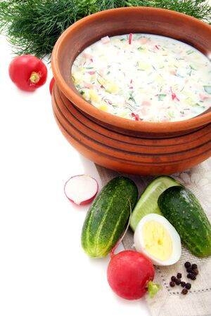 Cold yogurt soup with eggs, vegetables and meat in a ceramic bowl.