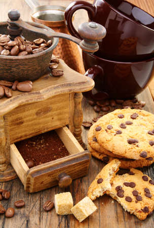 Coffee Mill, cups and biscuits on a wooden table.  photo