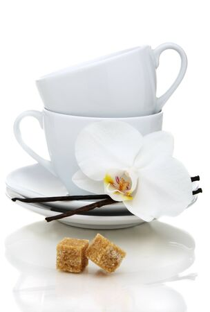 Tea cups, sugar and vanilla on a white background. photo