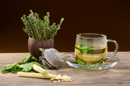 Tea strainer, and a cup of grass on a wooden table.