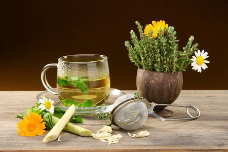 Medicinal herbs, flowers and herbal tea on a wooden table. photo