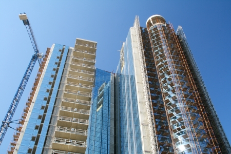 Modern high-rise building under construction on a background of blue sky