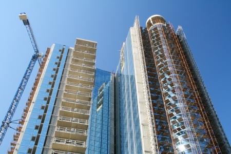 Nowoczesny wieżowiec w budowie na tle niebieskiego nieba
