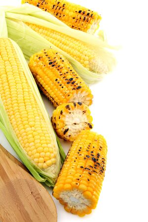 Cleaning freshly roasted ears of corn on cob with green leaves on a white background.
