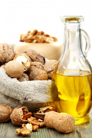 Walnut oil  and nuts in a bag on a wooden table   photo