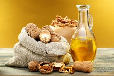 Walnut oil in bottle and nuts on a wooden table