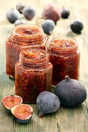 Figs and jam in glass jars on a wooden table