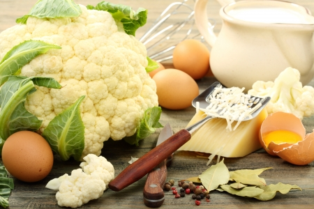 Cauliflower for baking with egg and cheese on a wooden board   Stock Photo