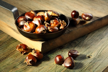 Roasted chestnuts on an old wooden table