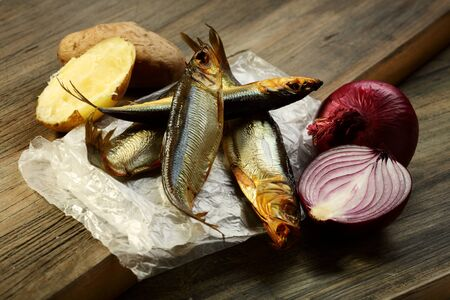 fishy: Smoked fish, potatoes and red onion on an old table  Stock Photo