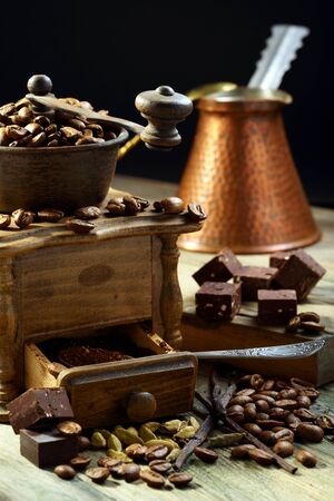 cezve: Old coffee grinder and coffee with cardamom on a wooden table  Stock Photo