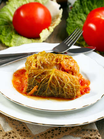 Stuffed cabbage with tomato sauce on a white plate  photo